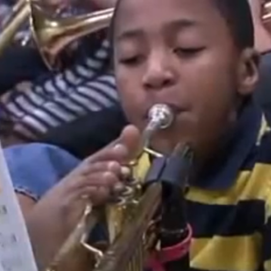boy with no arms plays trumpet